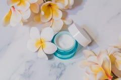 Skincare moisturiser produkt na marmuru stole z egzotycznym frangipani kwitnie fotografia royalty free