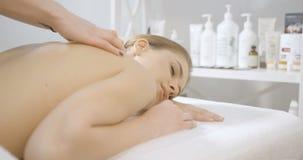 Skincare och hedbegrepp Händer av den kvinnliga massageren gör den tillbaka massagen för att le den härliga kvinnan i brunnsorten lager videofilmer