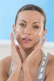Skincare produkter - härliga kvinnor som applicerar fuktighetsbevarande hudkräm Arkivfoton