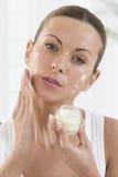 Skincare produkter - härliga kvinnor som applicerar fuktighetsbevarande hudkräm Fotografering för Bildbyråer
