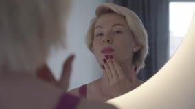 Skincare Retrato de una mujer que pone la crema hidratante en piel del problema envejecimiento almacen de video