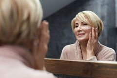 Free Skincare Routine. Mature Woman Uses Cosmetic Cream On Face Skin In Front Of The Mirror Reflection. Stock Image - 183603251