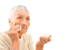 Skincare for the 80's. Very old lady isolated on white is wiping off her face with a makeup pad Stock Photo