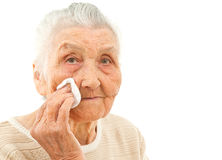 Skincare for the 80's. Very old lady isolated on white is wiping off her face with a makeup pad Royalty Free Stock Photo