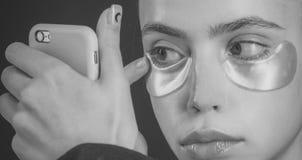 Skincare, spa, collagen mask under eyes gold color from wrinkles stock image