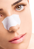 Skincare Strip on Nose. Vertical photo of a skincare strip, attached on a female nose. She has silky smooth skin and hazel eyes Stock Photos