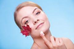 Skincare. Ung kvinna för framsida med kräm och bladet Arkivfoto