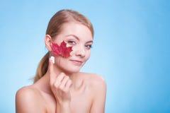 Skincare. Ung kvinna för framsida med kräm och bladet Fotografering för Bildbyråer