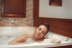 Skincare. Wellness. Beautiful Young woman relaxing in jacuzzi ba. Th spa, Attractive girl with Clean Fresh Skin relaxing foam bath in bathroom. Beauty face care Stock Photos