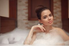 Skincare. Wellness. Young woman relaxing in jacuzzi bath spa, br. Unette enjoying foam bath in bathroom. Beauty skin care treatment. Beautiful model relax at Stock Photography