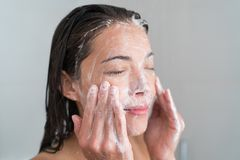 Skincare woman washing face in shower. Foaming facewash soap scrub on skin. Asian female adult cleaning body showering in hot water at home on in hotel as stock photos