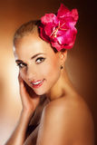 Closeup beautiful young woman face with flower. Girl smiling. Skincare of young beautiful woman face with fresh red flower. Girl smiling, looking at camera Stock Photos