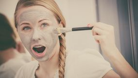Woman applying with brush clay mud mask to her face. Skincare. Young funny woman applying with brush grey clay mud mask to her face. Female taking care of skin Stock Photos