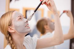 Woman applying with brush clay mud mask to her face. Skincare. Young playful woman applying with brush grey clay mud mask to her face. Female taking care of skin Stock Photo