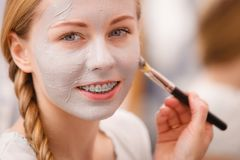 Woman applying with brush clay mud mask to her face Stock Photography