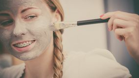 Woman applying with brush clay mud mask to her face. Skincare. Young woman applying with brush grey clay mud mask to her face. Female taking care of skin Royalty Free Stock Photos