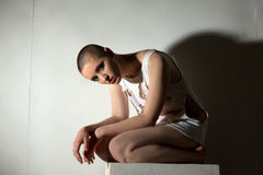 Skinhead girl posing as patient of lunatic asylum Royalty Free Stock Photography