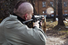 A skinhead male with the gun is threatening to someone behind the trees Royalty Free Stock Photos