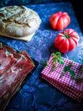 Skinka, bröd, tomater och nya örter i sammansättning på mörk bakgrund royaltyfri foto
