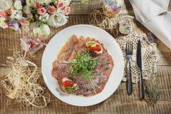 Skinka, körsbärsröda tomater, röd peppar och örter på den svarta stenen kritiserar Royaltyfri Fotografi