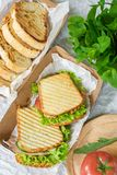 Skinkabr?d med den gr?nsaksallad och tomaten p? en tabell och ett papper arkivbilder