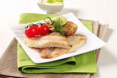 Skinless fish fillets with baked potato half Stock Image