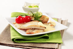 Skinless fish fillets with baked potato half Royalty Free Stock Image