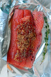 Skinned piece of salmon with spices, honey and thyme on aluminium foil Stock Photos