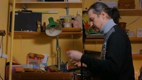 Skinner che lavora con la cinghia di cuoio video d archivio