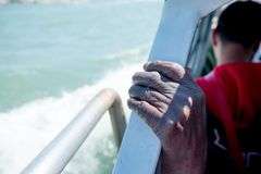 Close up of thin and skinny african migrant man hand on boat while crossing mediterranean sea to europe on sunny day. Skinny african migrant man hand on boat stock photo