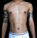 Skinny Asian guy body part with tattoos. On black background royalty free stock photography