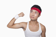Skinny athlete showing bicep Royalty Free Stock Image