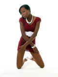 Skinny black woman kneeling in red dress Stock Image