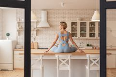 Skinny blonde woman sitting on table in lotus pose stock photography