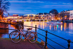 Skinny bridge and Amstel river in Amsterdam Netherlands at Dusk. Selective foreground focus on bicycles Royalty Free Stock Photo