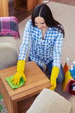 Skinny brunette cleaning with mop small coffee table Royalty Free Stock Photography