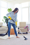 Skinny brunette cleaning with vacuum cleaner carpet Royalty Free Stock Photo