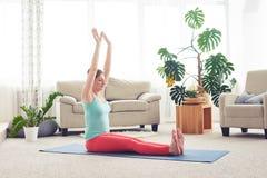 Skinny female sitting on yoga mat and practicing yoga Stock Photo