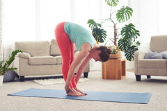 Skinny female stretching on yoga mate in living room Royalty Free Stock Images
