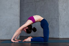 Skinny flexible female yogini bending backwards doing stretching exercises on floor in a room Royalty Free Stock Image