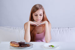 Skinny girl can't eat sweets Stock Photos