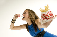 Skinny girl eating french fries Stock Photos