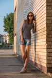Skinny Girl Posing Leaning Against The Yellow Brick Wall On A Playground Royalty Free Stock Images