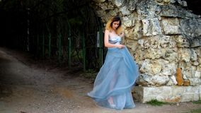 Skinny girl in silver and blue dress in high heeled shoes stands near stony wall of arc and dances as gipsy preparing to stock video