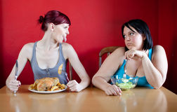 Skinny girl with a whole chicken teasing fat girl Royalty Free Stock Photography