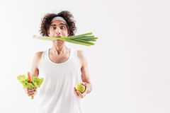 Skinny guy eats only vegetables Royalty Free Stock Photos