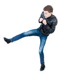 Skinny guy funny fights waving his arms and legs. Isolated over white background. The boy timidly is kicked. Clumsy guy fights feet Stock Image