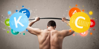 Skinny guy lifting colorful vitamin weights Royalty Free Stock Photography
