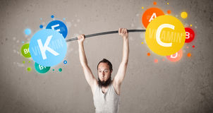 Skinny guy lifting colorful vitamin weights Royalty Free Stock Photos
