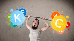 Skinny guy lifting colorful vitamin weights Stock Photos